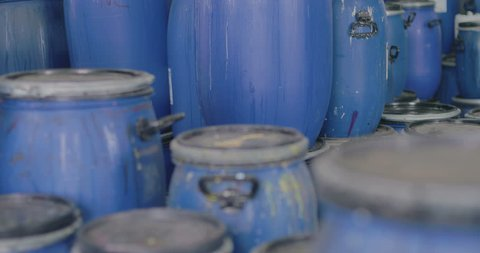 A large number of plastic barrels with an unknown liquid. Tracking shot. in slow motion