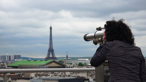 Female person looks at Paris cityscape with help of Coin Operated Binocular on top of Galery Laffaete. Over shoulder camera