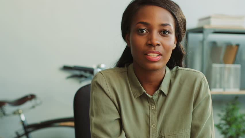 Portrait of attractive business african woman in casual khaki shirt smiling and talking to the camera on the modern office background. Close up