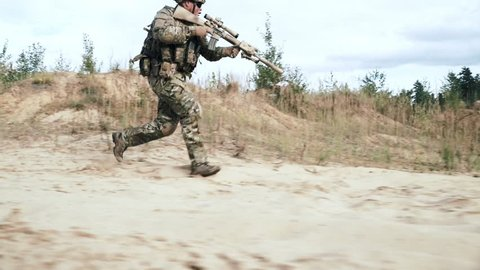 Military soldier with sniper rifle running on sand side view. Military soldier with weapon running on sand sand