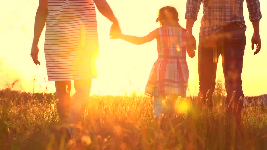 Happy Young Family with child walking on summer field. Healthy mother, father and little daughter girl enjoying nature together, outdoors. Slow motion. 4K UHD video 3840X2160