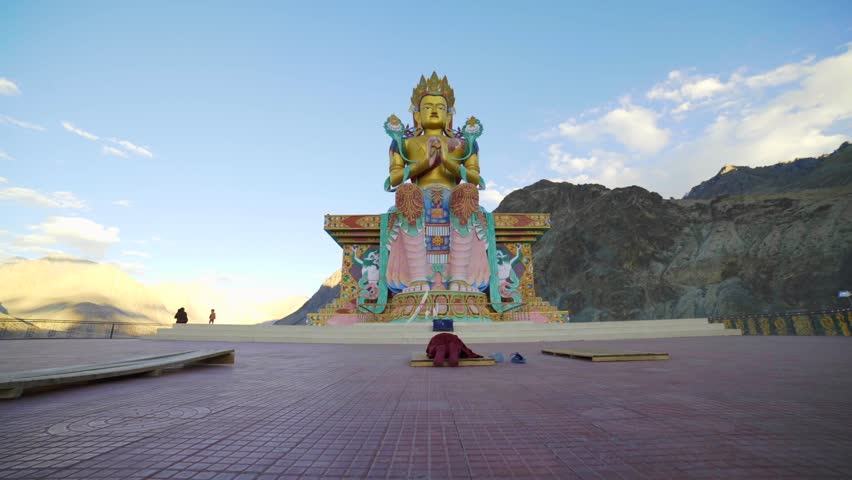 A buddhist monk praying to a giant Buddha Statue, in India.