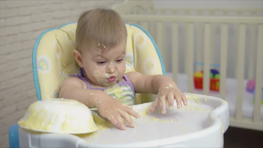 A small child alone eats baby food with a spoon from a saucer spilling into porridge