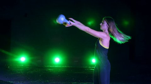 Athletic, beautiful, young woman doing various strength exercises with weights. At night, in light of multi-colored searchlights, in light smoke, fog, in an old abandoned hangar