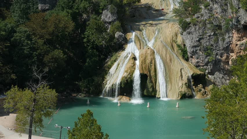 Steady medium wide shot of Turner Falls on a bright sunny day  The 77-foot Turner Falls is one of the most popular summer destinations in Davis, Oklahoma