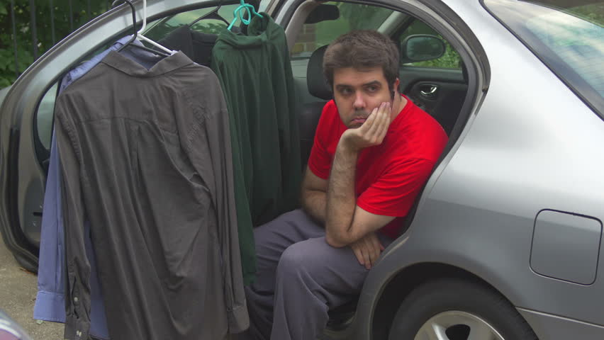 Young Handsome Man Sits In Car Trunk And Phones With Smartphone