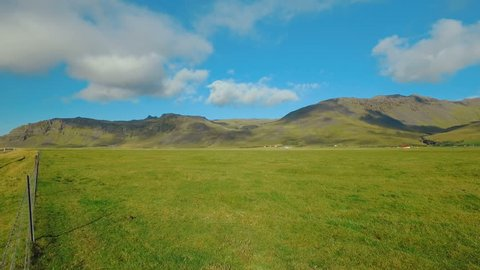 panorama of picturesque green fields and static clouds in Iceland, near volcano Eyjafjallajokull