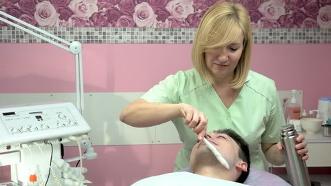 Face cryomassage, young man. Female cosmetician using liquid nitrogen. Pros and cons of cryotherapy.