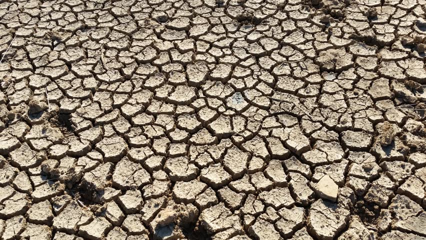 Hot drought cracked clay mud dust pan of dry river bed stock dry cracked earth during climate change drought disaster 4k stock video clip sciox Images