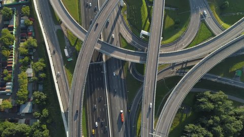 Multi-level road junction and cars traffic. Camera is tilting up. Aerial vertical shot.