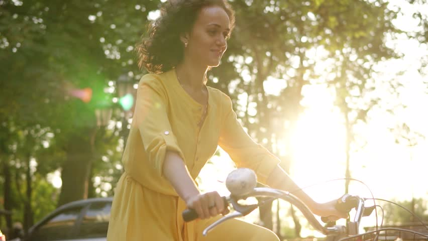 Lens flare: smiling happy woman in long yellow dress is riding a city bicycle with a basket and flowers in the park with green trees around during the dawn. Slowmotion shot