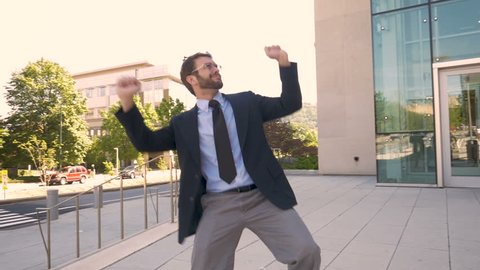 Handsome male business executive with a beard silly victory dancing his success and achievement in slow motion outside his office building