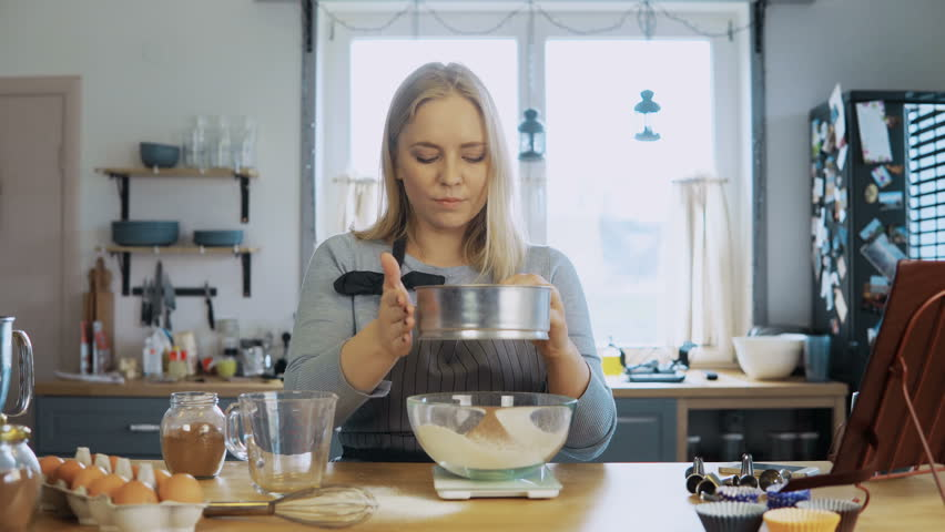 Young beautiful woman weighs the cocoa, adds to flour. Girl using kitchen scales, bowl and sieve for this.