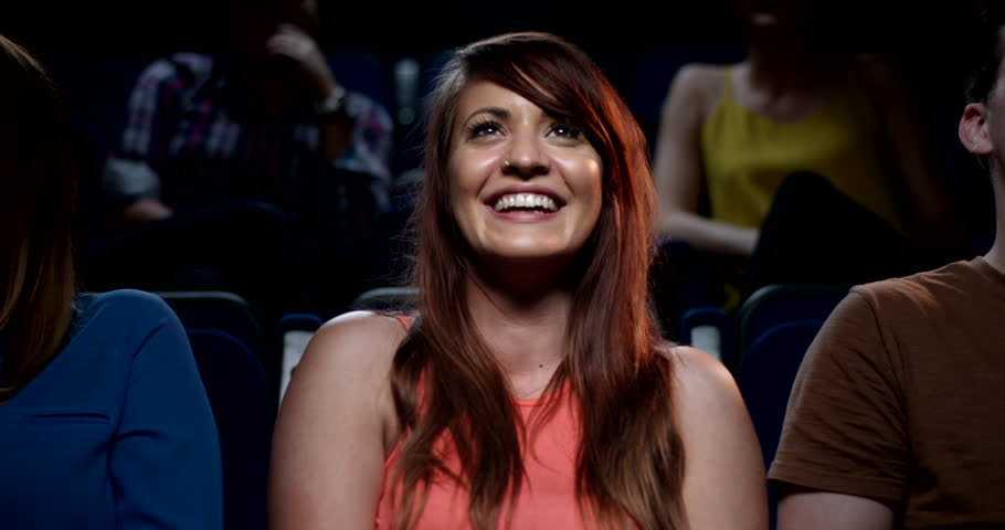A beautiful young woman smiling and laughing in a movie theatre