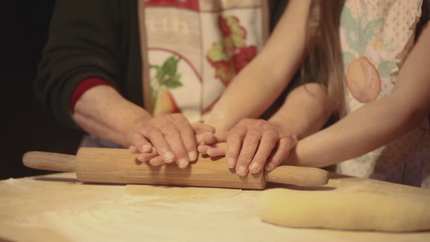 Gorgeous vintage slow motion of an elderly woman a young girl preparing pasta or pizza together using a rolling pin on a sheet of kneading. #30452452