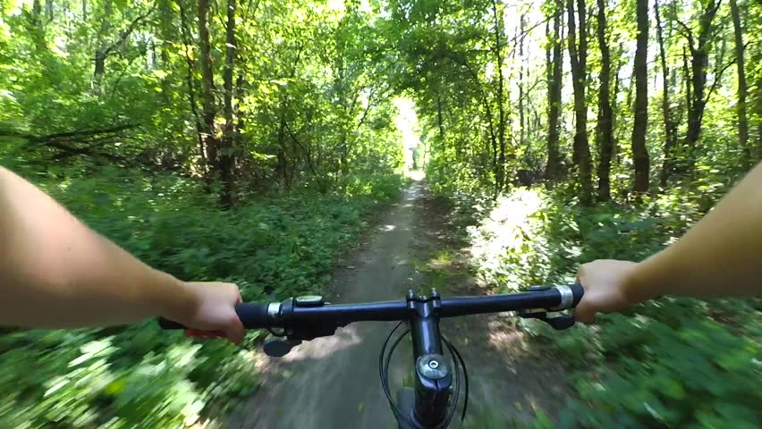 Girl rides a bike along a path in a pine forest in the summer with sunlight. POV. Caucasian. Action camera go pro. Concept Adventure Active Lifestyle Sports. View from first person perspective. | Shutterstock HD Video #30464998