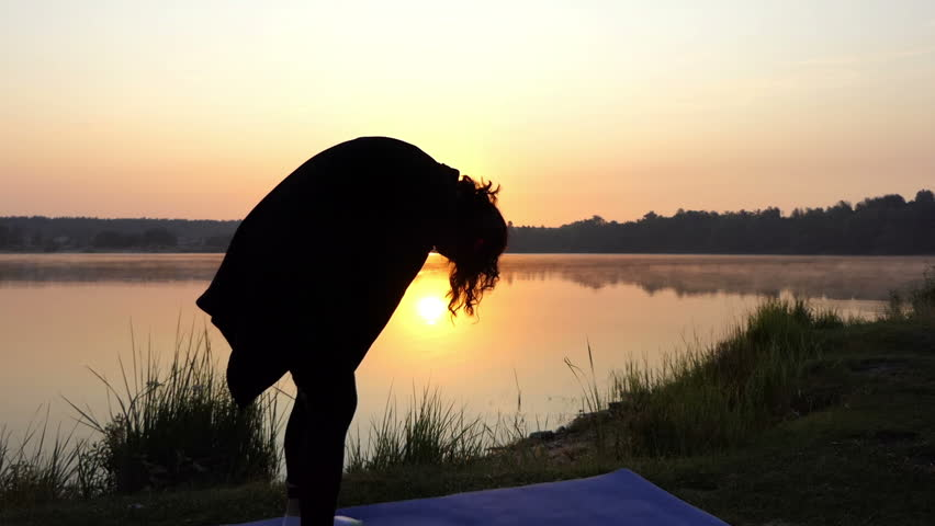 Breathing Exercises of Two Young Women Standing on Their Yoga Mats at a Nice Sunset Near a Wild Lake in Eastern Europe in the Evening in Summer in Slow Motion.the Landscape Looks Unusual and Rough | Shutterstock HD Video #30467842