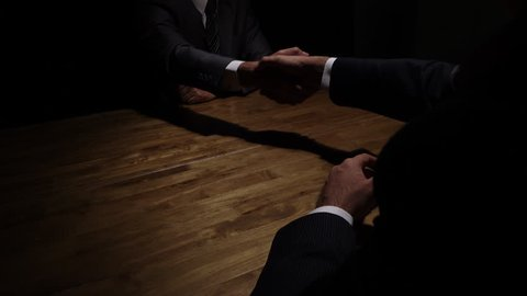 Two businessmen making handshake in the dark after finishing negotiation for a deal