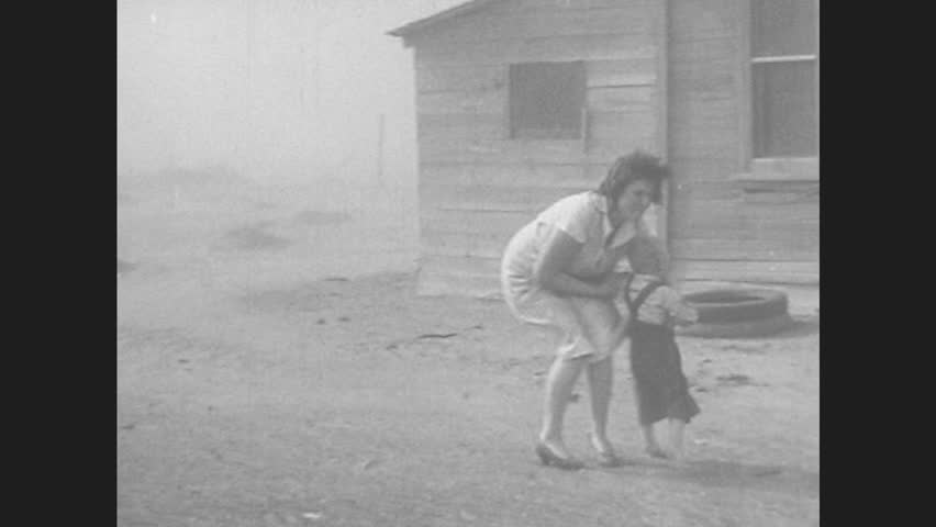 1940s: UNITED STATES: lady picks up baby from yard during dust storm. Vehicles buried under dust in field. Lady runs to house in storm. Man runs to house. Sand piled up by building