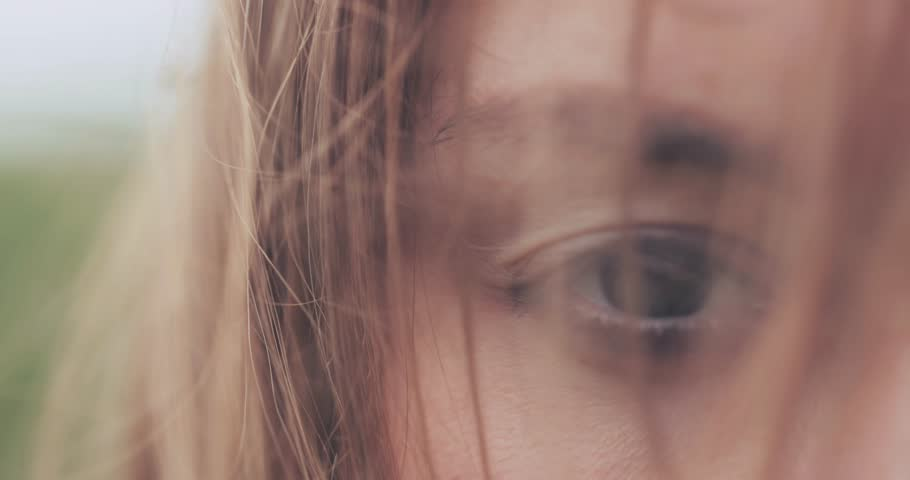 Close Up of Woman Eyes Covered with Hair Blowing on the Wind. SLOW MOTION 4K DCi. Green Eyes. Determined Female Sight. Stormy weather, autumn, winter, spring.