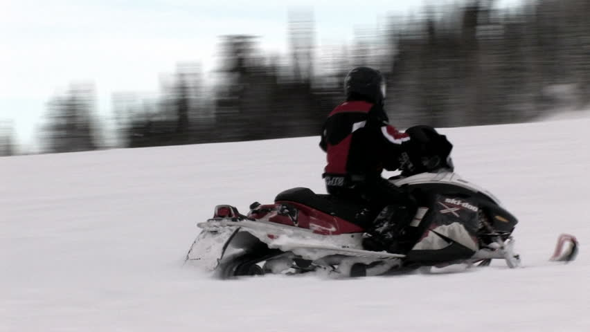 Snowmobile operator drives up a hill in central Utah. Rider wearing red and black as well as a safety helmet. Winter recreation.