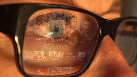 STOCKHOLM - SEPTEMBER 7, 2017: A woman watching Netflix, an online streaming service for movies and series, with an animated screen reflection displayed in her glasses.
