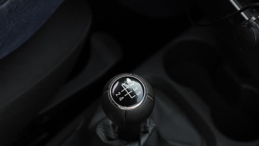 manual gear shift knob on a vehicle. hand of driver, driving car shifting gears