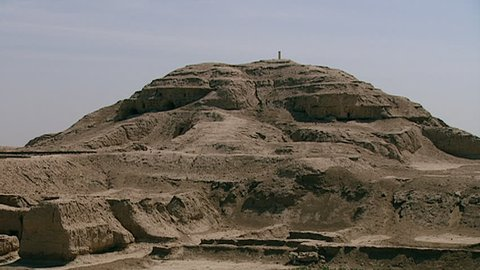 WARKA, IRAQ - CIRCA 2002: Ziggurat with Stone-Cone temple ruins in the foreground, part of the Eanna district dedicated to Sumerian goddess Inanna. Uruk is one of the first cities in history.