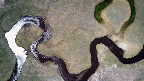 Aerial shot of small curvy river and green meadow.