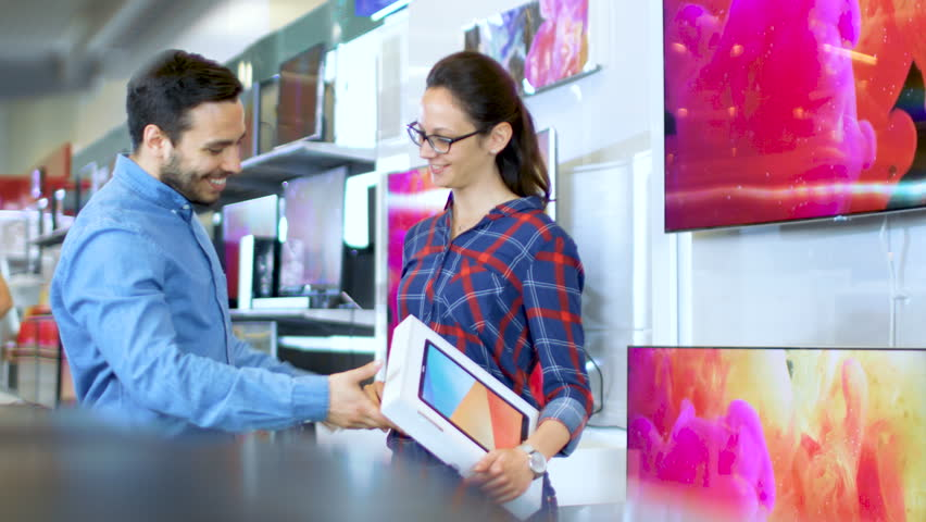 Young Couple In the Electronics Store Purchased Latest Model of a Tablet Computer, They're Very Much in Love and are Incredibly Happy. Store is Bright and Modern, Has all The Latest Devices. 4K UHD. | Shutterstock HD Video #30542242