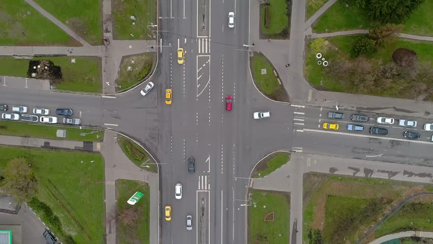 Top view of the road junctions. Aerial survey of highways of the road network. Machines moving at the intersection and denouement. Organization of traffic from a bird's eye view. Spring road.