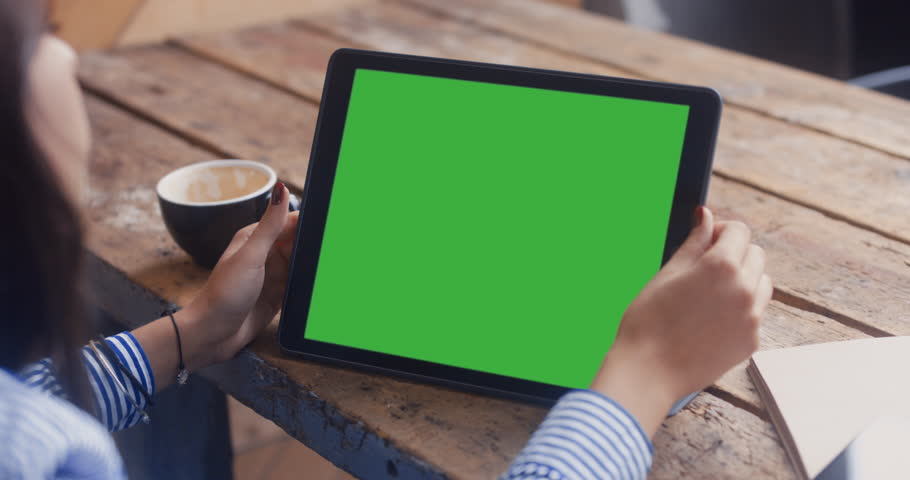 GREEN SCREEN Over the shoulder shot of young Caucasian female with long black hair using digital tablet. 4K UHD 60 FPS | Shutterstock HD Video #30553372