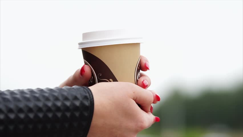 Close-up outdoor shot of female hands getting warm with a cup of hot coffee