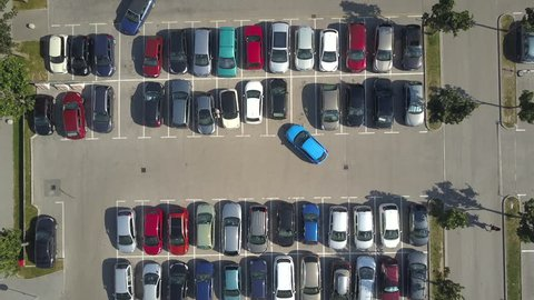 AERIAL TOP DOWN, HYPERLAPSE: Bad driver incapable to park a car on parking space in big crowded parking lot. Female having problems, unable to park a car in parking spot. Parking fail on parkspace