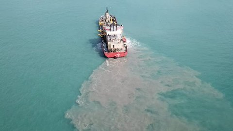 Haifa, Israe - 9 September, 2017: EDT SIMI Suction Dredger ship working near the port - with mud, Pollution, brown Muddy water - aerial shot