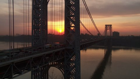 (Time-lapse) The sun rises while morning rush hour traffic on the George Washington Bridge crosses the Hudson River between New Jersey and New York.
