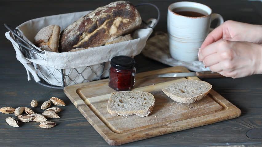Spreading blueberry blackberry blackcurrant jam on crunchy toast in slow motion