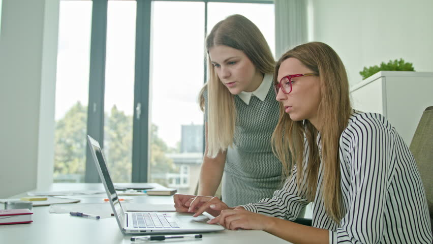 Two woman in modern start up office female team leader pointing at screen discussing diverse people group teamwork using laptop display   Shutterstock HD Video #30583336