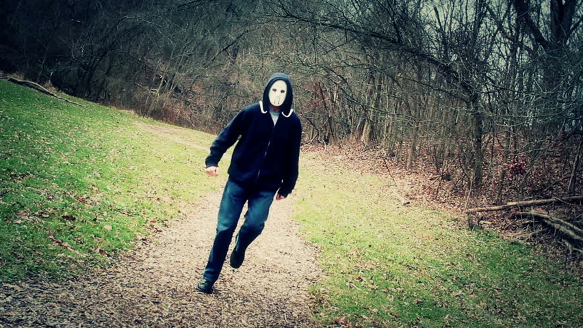 A masked killer happily skips down a wintry forest trail.