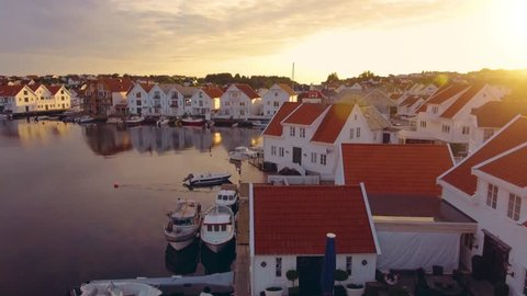 Flight over amazing city of Norway with beautiful harbor and city infrastructure at sunset. Top view of cozy port city Skudeneshavn, Norway. Beautiful white yachts and boats stand in the sea harbor.
