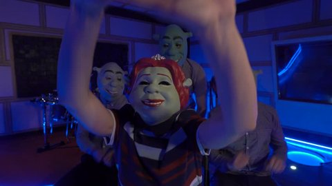 Three Shrek and Fiona claps their hand, sings song, dancing, laughing. People in the masks of shrek have fun with girl