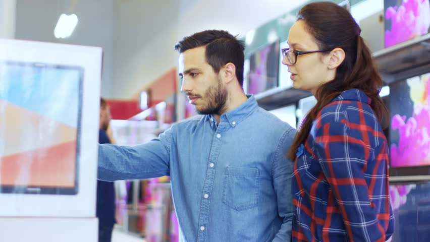 Beautiful Young Couple in the Electronics Store Browsing, Looking for Newest Gadgets, Tablets and Photo/ Video Cameras Presented on the Shelves. Shot on RED EPIC-W 8K Helium Cinema Camera. | Shutterstock HD Video #30614521