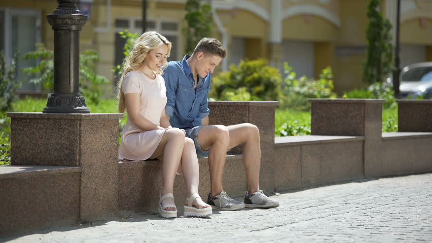 Male and female sitting on bench next to each other, feeling awkward, first date