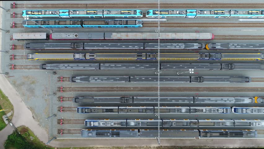 Aerial moving right above railway hub showing passenger trains on tracks next to each other top down view drone moving slowly showing railway tracks positioned horizontally above each other 4k quality