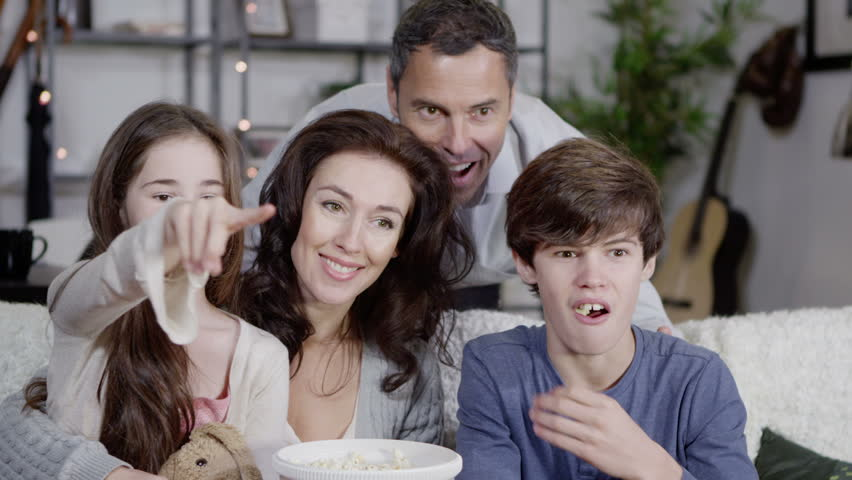 Happy caucasian family watching television and chatting as they eat popcorn together at home. In slow motion