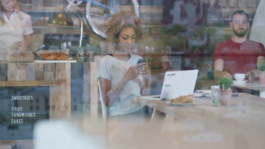 Professional woman using laptop in city cafe & waitress taking payment at the table