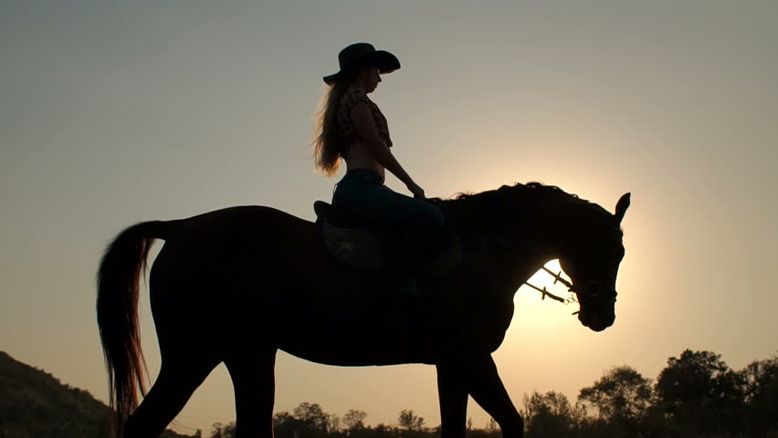 Close-up silhouette of a young girl in a cowboy hat riding a horse on sunset sky background. Slow motion. #30653542