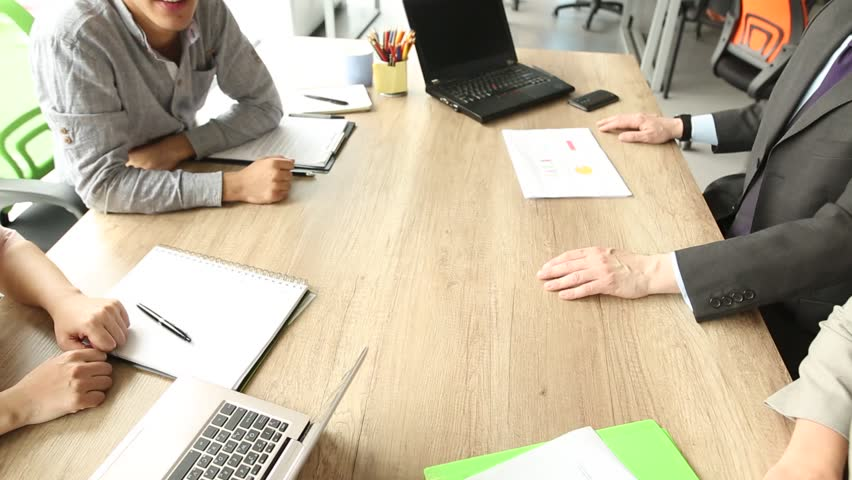 Close up view of business team sitting at the table in the office, folding hands. Work is done, happy coworkers holding hands together.   Shutterstock HD Video #30656563