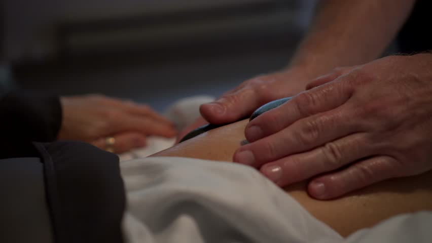 Very tight shot of massage therapist using two smooth black stones on the  thigh of a mature caucasian woman's