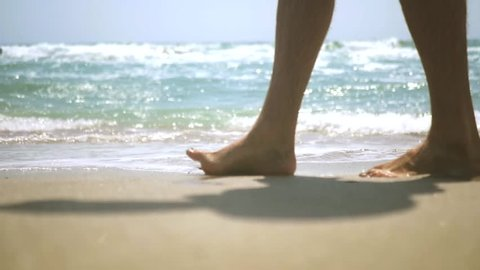 Walking along a sandy beach by the sea and beautiful waves, close-up. HD, 1920x1080. slow motion.